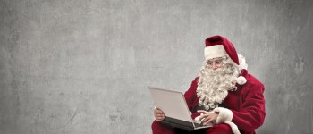 Santa Claus using a laptop computer in a white dark room